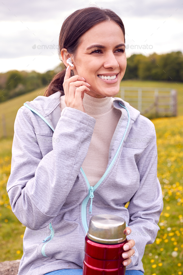 Woman Sitting On Bench In Countryside Relaxing And Listening To Music Or Podcast On Earphones - Stock Photo - Images