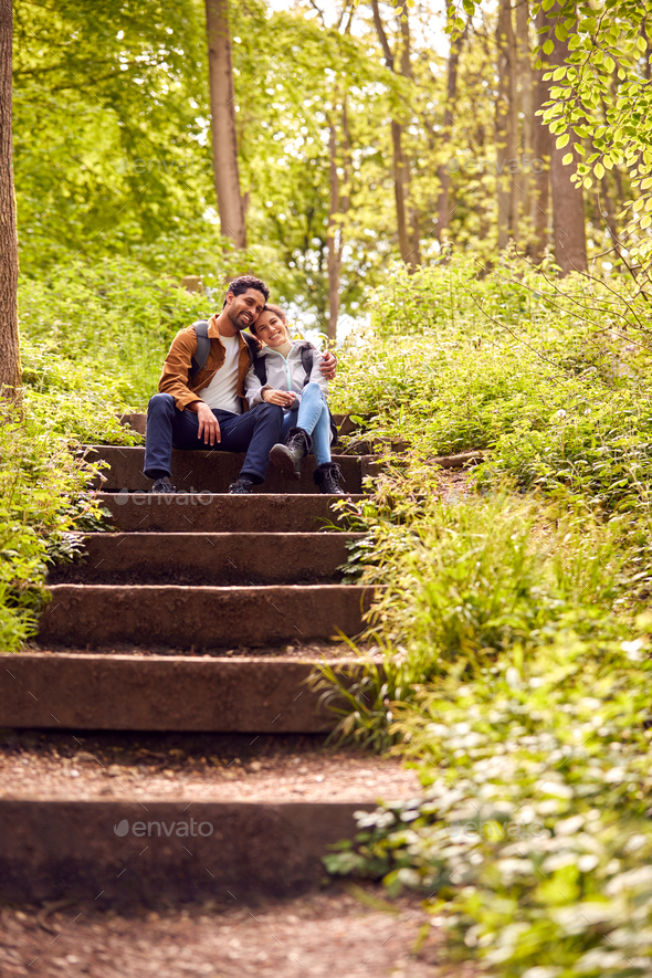 Hiking Couple With Backpacks Sitting On Steps On Path Through Trees In Countryside Together - Stock Photo - Images