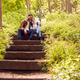 Hiking Couple With Backpacks Sitting On Steps On Path Through Trees In Countryside Together - PhotoDune Item for Sale