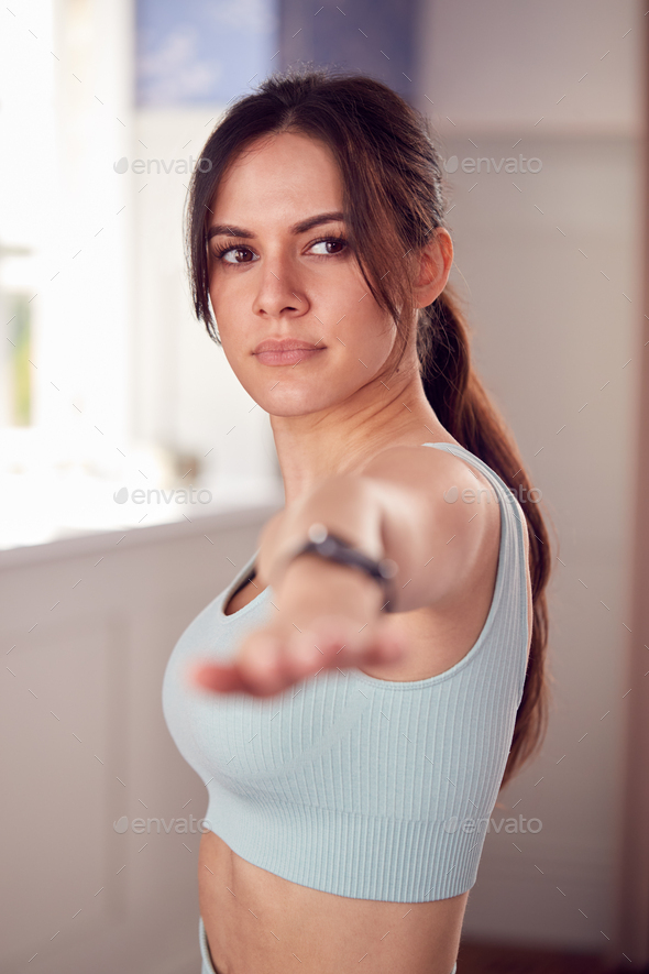 Woman Doing Yoga Wearing Fitness Clothing And Activity Monitor Stretching In Bedroom At Home - Stock Photo - Images