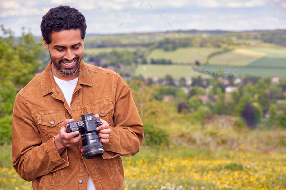 Man With Digital DSLR Camera Taking Photos In Countryside - Stock Photo - Images