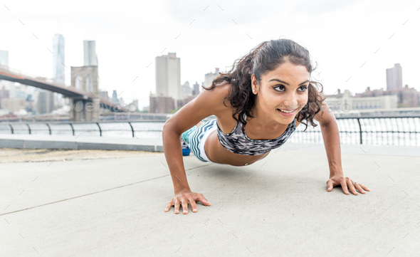 Woman making push up training in New york city - Stock Photo - Images