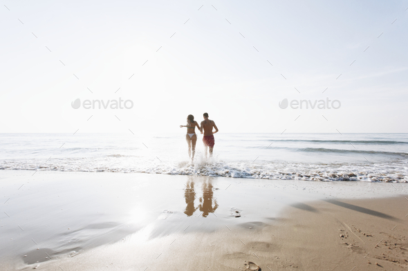 Cheerful couple running at the beach - Stock Photo - Images