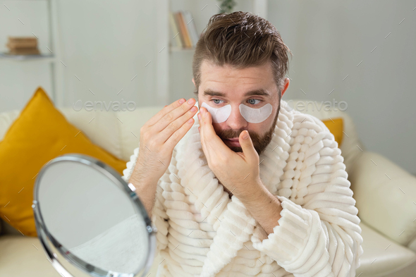 Bearded man applying eye patches on his face. Wrinkles and face home care for men - Stock Photo - Images