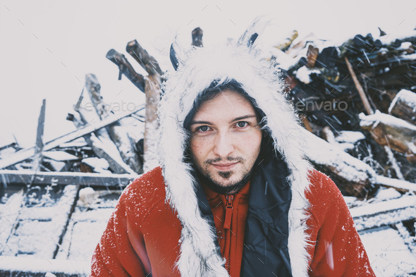 Young man enjoying a snowy day wearing a fur hat and a red hoodie - Stock Photo - Images