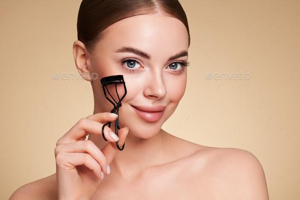 Beautiful woman using eyelash curler - Stock Photo - Images
