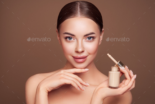 Portrait beautiful young woman with foundation bottle - Stock Photo - Images