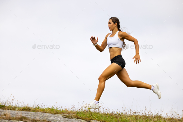 Determined Fit Female Athlete Running On Mountain Against Sky - Stock Photo - Images