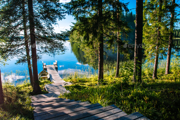 Wooden pier with bench for rest on a blue lake in Finland - Stock Photo - Images