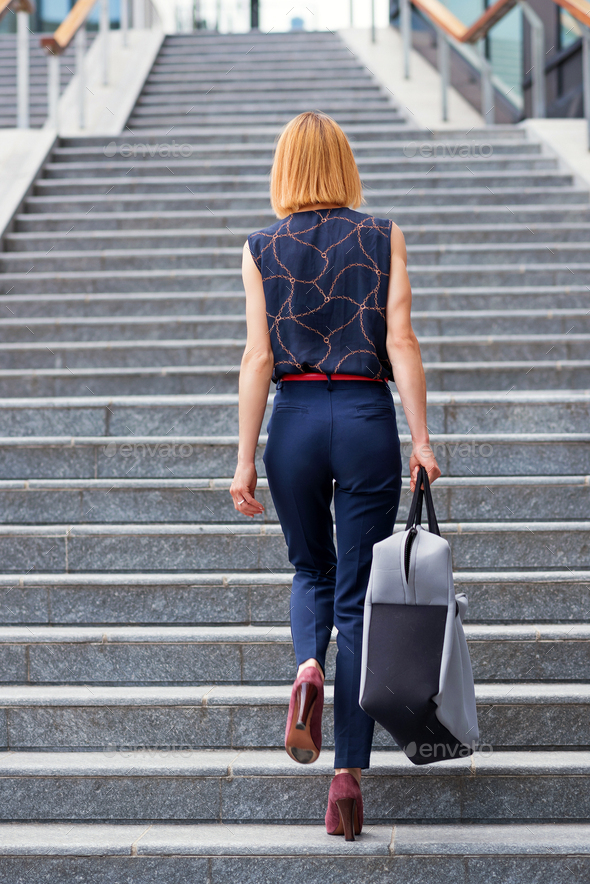Slender stylish woman walking up a flight of stairs in town - Stock Photo - Images