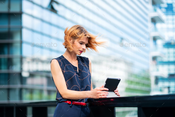 Attractive stylish woman standing watching media on her tablet - Stock Photo - Images