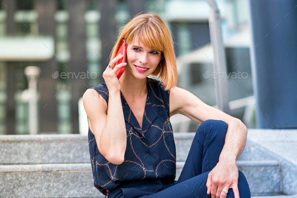 Attractive stylish woman smiling as she chats on a mobile - Stock Photo - Images