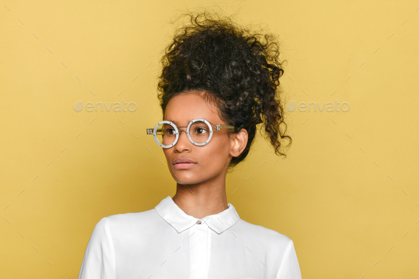 Trendy black girl in stylish retro round glasses with hair up - Stock Photo - Images