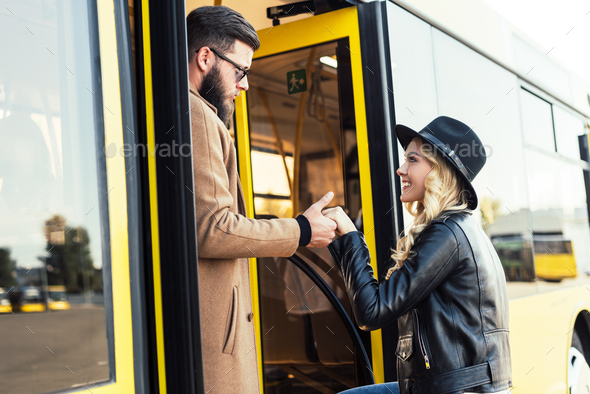 side view of man helping girlfriend to enter city bus - Stock Photo - Images