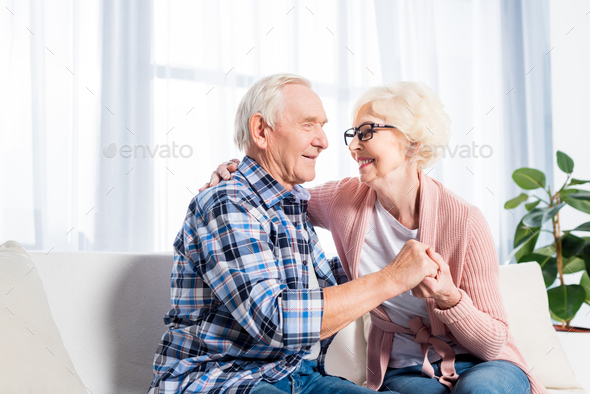 happy senior couple looking at each other and holding hands at home - Stock Photo - Images