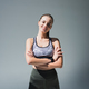 cheerful sporty girl standing with crossed arms and smiling at camera on grey - PhotoDune Item for Sale