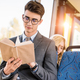 handsome young businessman in eyeglasses reading book in city bus - PhotoDune Item for Sale