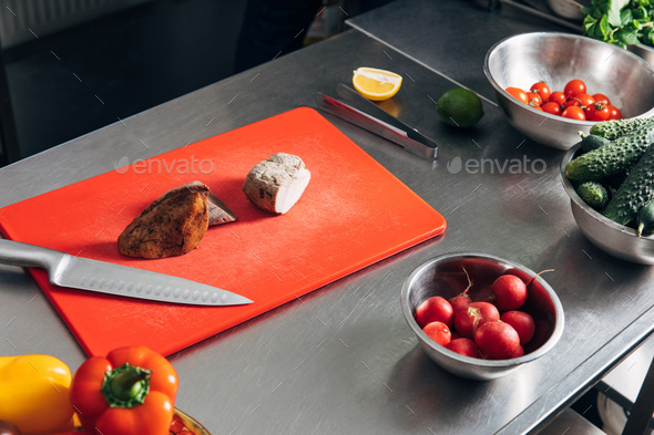 sliced meat on cutting board with vegetables at restaurant kitchen - Stock Photo - Images