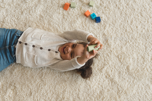 overhead view of happy little girl playing with cubes at home - Stock Photo - Images