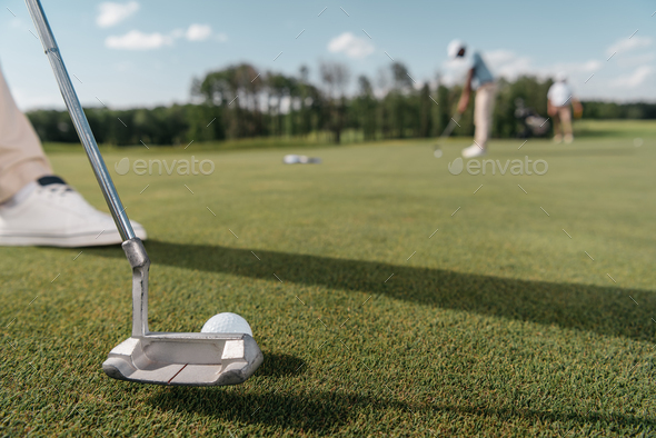close up of golf club and ball before shot on green - Stock Photo - Images