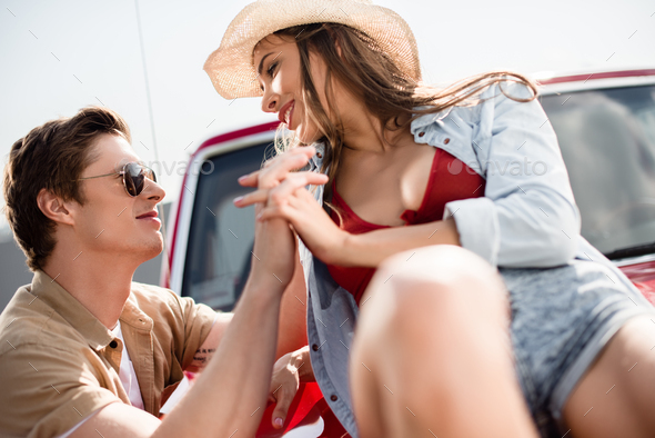 close-up view of young couple in love holding hands and smiling each other - Stock Photo - Images