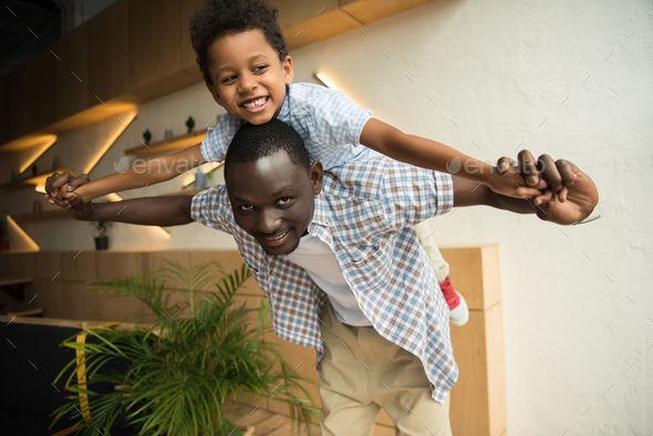 happy african american father piggybacking adorable little son indoors - Stock Photo - Images