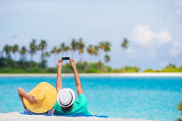 Happy couple taking a photo on white beach on honeymoon holiday - Stock Photo - Images