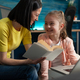Caucasian mother helping girl with homework project - PhotoDune Item for Sale