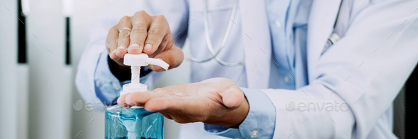 Doctor pressed his hand on the bottle of hand sanitizer. - Stock Photo - Images