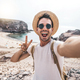 Young man with backpack taking selfie portrait on a mountain - PhotoDune Item for Sale