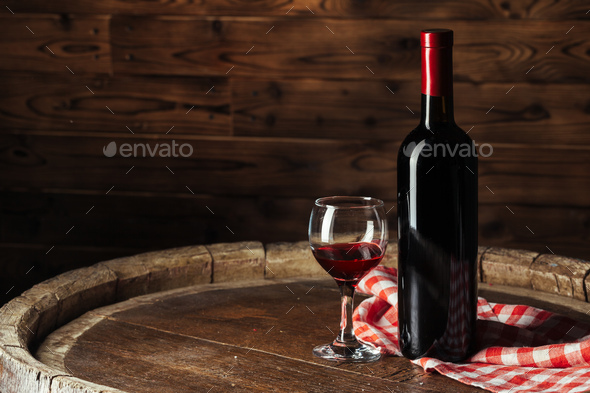 Bottle and glass of red wine on wooden barrel shot with dark wooden background - Stock Photo - Images