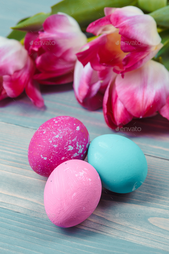 Easter eggs with tulips on blue wooden background - Stock Photo - Images