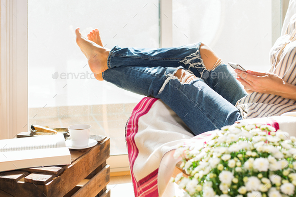 Young woman is relaxing at home, drinking tea, reading book - Stock Photo - Images