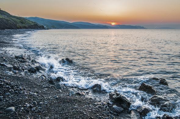 Sunset on the seashore, rocky beach - Stock Photo - Images