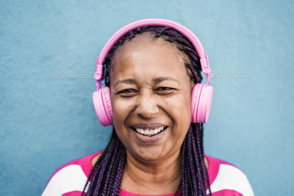Senior african girl listen playlist music with headphones - Focus on face - Stock Photo - Images