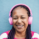 Senior african girl listen playlist music with headphones - Focus on face - PhotoDune Item for Sale
