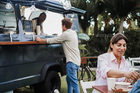 Multiracial people eating at food truck restaurant outdoor - Focus on hispanic woman face - Stock Photo - Images