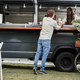Young man ordering food at counter in food truck outdoor - Soft focus on chef woman face - PhotoDune Item for Sale