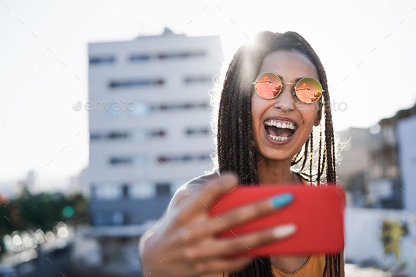 Bohemian girl doing selfie with mobile phone outdoor with city in background - Focus on face - Stock Photo - Images