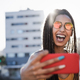 Bohemian girl doing selfie with mobile phone outdoor with city in background - Focus on face - PhotoDune Item for Sale