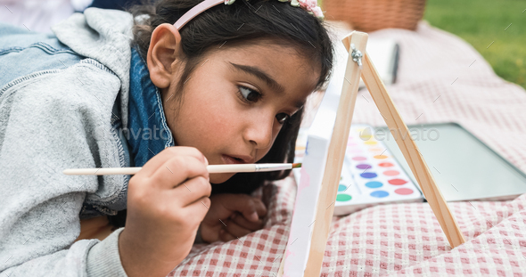 Happy indian little girl having fun painting outdoor at city park - Main focus on girl face - Stock Photo - Images