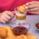 Close up on human hand of mature woman enjoying breakfast with fresh croissant and cappuccino - PhotoDune Item for Sale