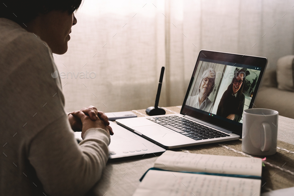 Young woman having video call with her colleagues using computer app - Multi generational business - Stock Photo - Images