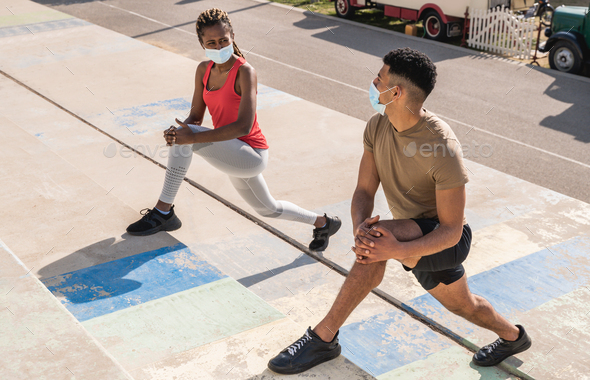 Young multiracial fit people doing workout routine outdoor while wearing safty mask - Stock Photo - Images