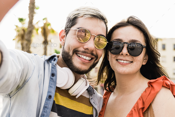 Happy hipster couple taking selfie during travel summer vacation outdoor in the city - Stock Photo - Images
