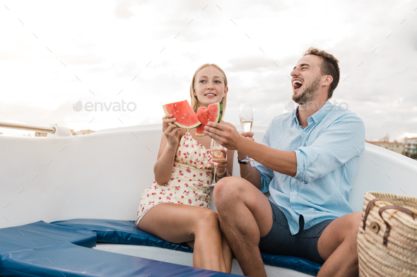 Happy young couple cheering with champagne and eating fruits on sail boat in summer vacation - Stock Photo - Images