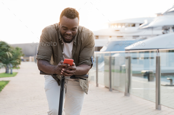 Young african man having fun driving electric scooter while using smartphone during summer vacation - Stock Photo - Images