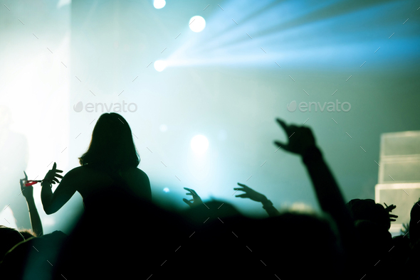 Rear view of crowd with arms outstretched at concert. Bright stage lights in the background - Stock Photo - Images