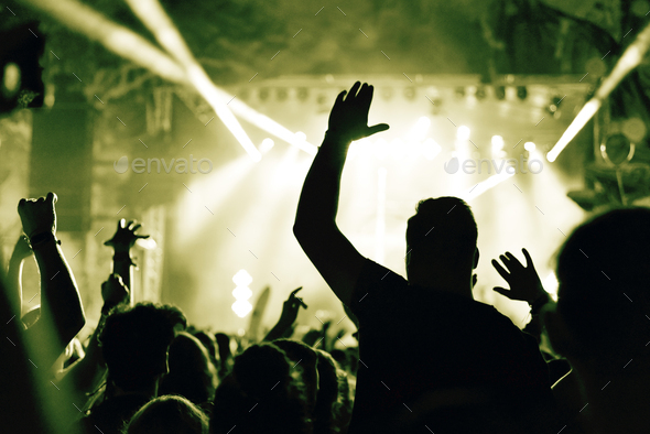 Crowd at a music concert with raising hands up, toned image - Stock Photo - Images