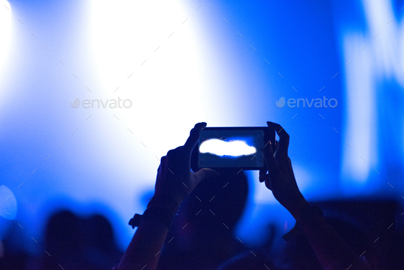 Hand holding smart phone at live music festival. Concert stage lights on viewfinder - Stock Photo - Images